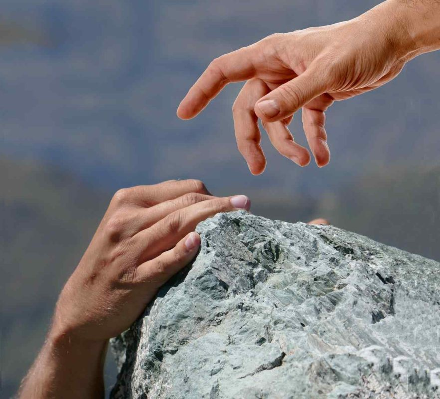 hand helping rock climber